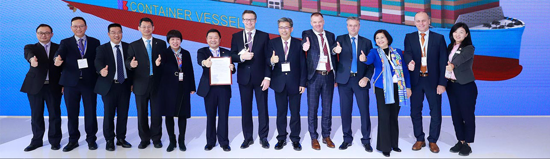 Knut Ørbeck-Nilssen (7th from left), CEO DNV GL – Maritime, presented the certificate to Chen Jun, President of Hudong-Zhonghua (6th from left), at the CSSC booth in Shanghai. The witnesses included Chen Jianliang, Hudong-Zhonghua Chairman (8th from left), and Norbert Kray, DNV GL – Maritime Regional Manager for Greater China (9th from left), alongside executive members from both companies.